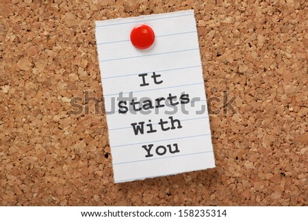 The words It Starts With You typed on a scrap of lined paper and pinned to a cork notice board. A concept for customer service or self improvement, adapting to change or making plans. - stock photo