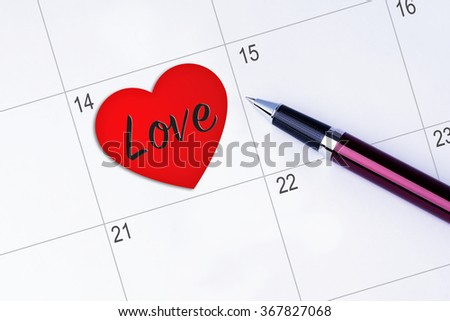 The words Love inside a Heart Shape written on a calendar planner to remind you an important appointment with a pen on isolated white background. Valentine's Day and Love Concepts - stock photo
