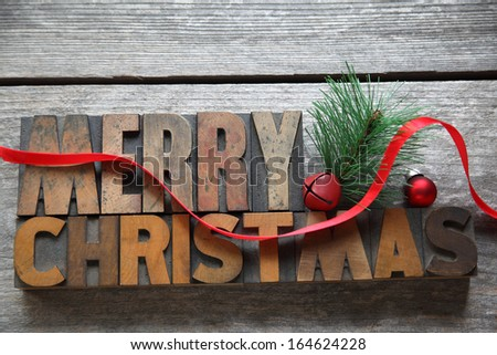 the words Merry Christmas with red ribbon on an old wood surface - stock photo