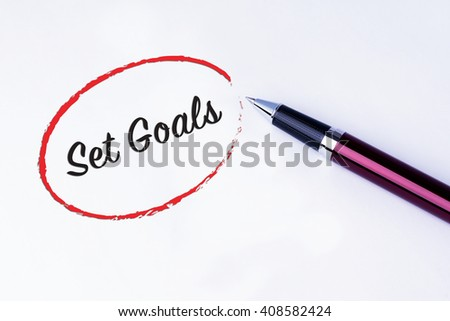 The words Set Goals written in a red circle to remind you an important appointment with a pen on isolated white background. New Year concepts of goal and objective. - stock photo