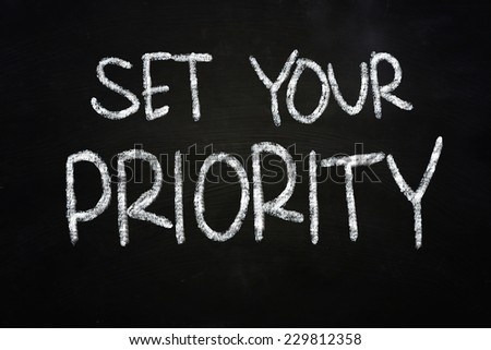 The words Set your priority written with chalk on blackboard - stock photo