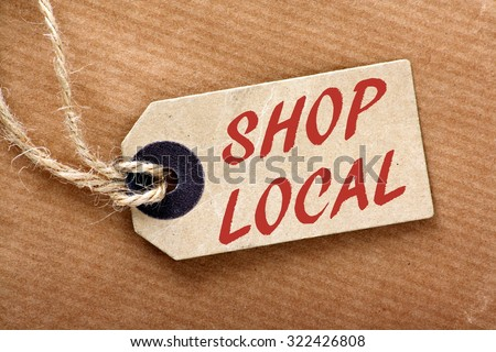 The words Shop Local in red text on a brown paper price label or luggage tag with string and wrapping paper - stock photo