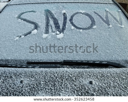 The words snow written on the windshield through the snow - stock photo