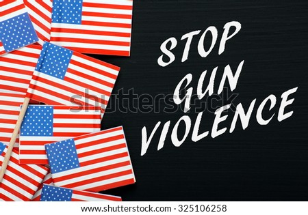 The words Stop Gun Violence in white text on a blackboard alongside miniature flags of the United States of America - stock photo