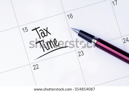 The words Tax Time on a calendar planner to remind you an important appointment with a pen on isolated white background.