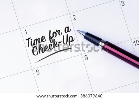 The words Time for a Check-Up written on a calendar planner to remind you an important appointment with a pen on isolated white background.  - stock photo
