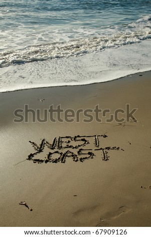 """the words """"West Coast"""" written in wet sand  on a secluded beach in """"southern california"""" with the tide of the pacific ocean and blue sky in the background - stock photo"""
