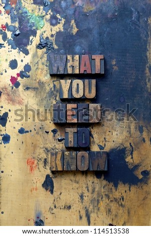 The words What you need to know written in very old and well used letterpress type. - stock photo