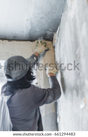 The worker covers with a mortar a concrete wall. Repair in a new apartment