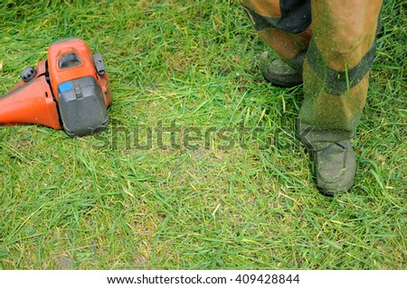 The worker cuts a grass on a site backyard. Male legs in a uniform of the worker of the lawn-mower. The part of a manual lawn-mower lies on a mowed grass.