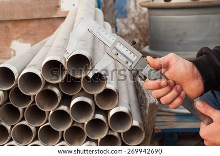 The worker does measurement of diameter of a pipe by means of a caliper - stock photo