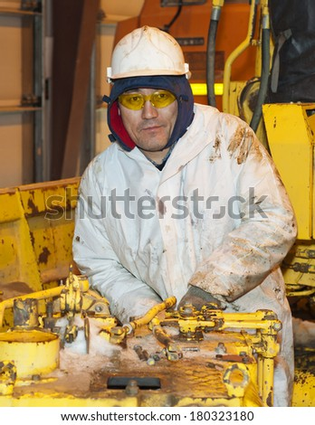 The worker dressed in a protective suit, repairs the transmission mechanism. - stock photo