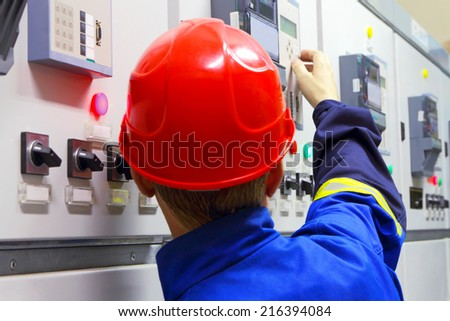 The worker in a helmet, the electrician - stock photo
