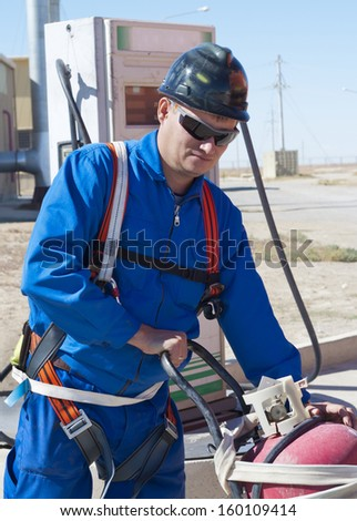 the worker in a uniform moves the big fire extinguisher on a production site - stock photo