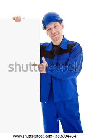The worker in blue uniform and safety helmet pointing on blank sign billboard, isolated on white