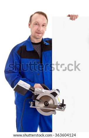 The worker in blue uniform with circular power saw in his hand holding blank sign billboard, isolated on white