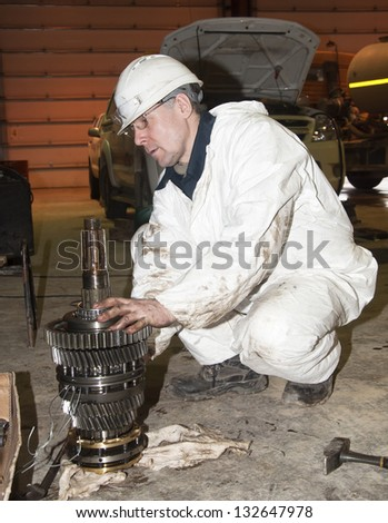 the worker in protective clothes repairs the automobile mechanism - stock photo