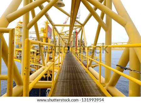 the worker is walking cross the pathway bridge of offshore oil rig - stock photo