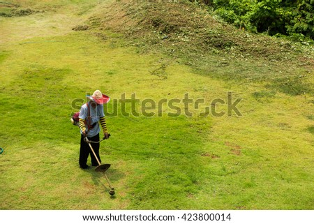 The worker of a garden cuts off a grass.Man mows the grass trimmer. - stock photo