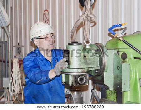 The worker operates the production equipment - stock photo