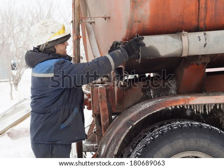 The worker prepares the drain device for pumping of fuel from a tanker