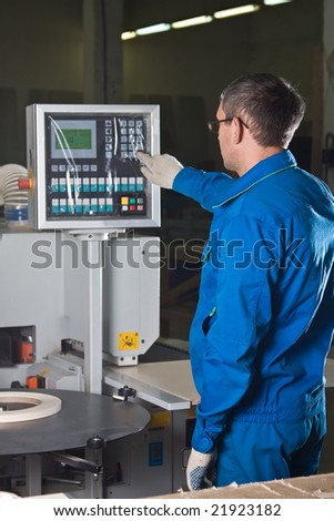 The worker presses buttons of the panel of the machine tool with numerical programmed control