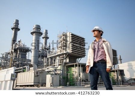 The worker standing in front of power plant station - stock photo