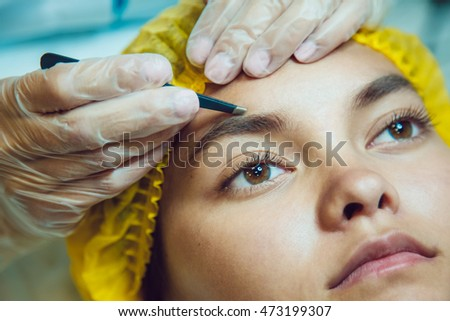 The workflow in a beauty salon girl plucked eyebrows. Tweezers.