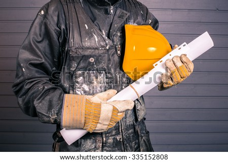 The workman holds in his hand a yellow protective helmet and construction drawings in Finland. The Worker's coverall is dirty. Image includes a effect.