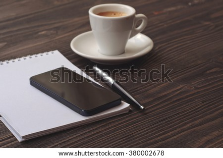 the workplace black smart phone with notebook, pen and cup coffee