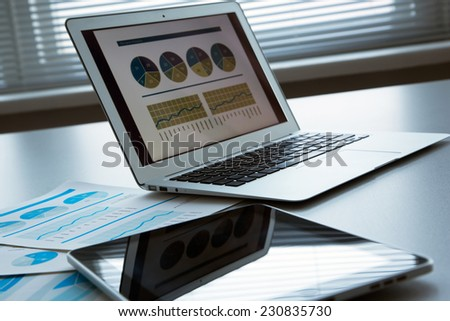 The workplace of business people. Laptop, raphs, charts, business table. - stock photo