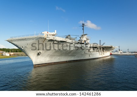 The World War II era aircraft carrier USS Yorktown, docked in the Charleston, SC Harbor with dramatic blue skies and reflections in the water