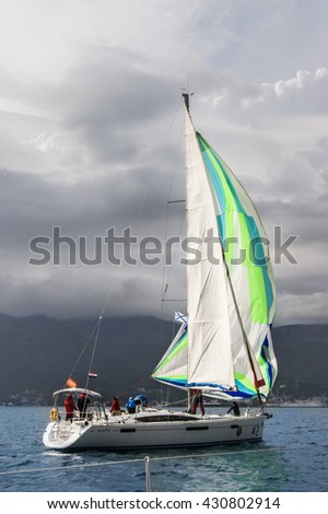 """The yacht on the background of gray clouds. Tivat, Montenegro - 26 April, 2016. Regatta """"Russian stream"""" in God-Katorskaya bay of the Adriatic Sea off the coast of Montenegro. - stock photo"""