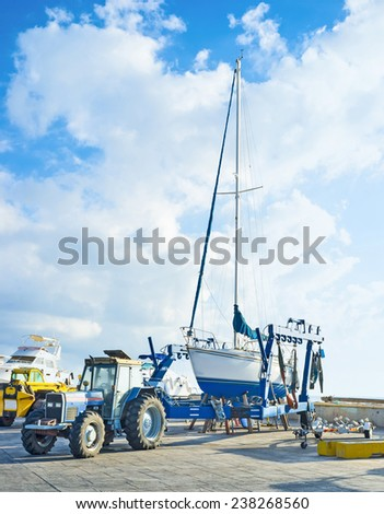 The yacht stands on the boat trailer in port of Latchi, Cyprus. - stock photo
