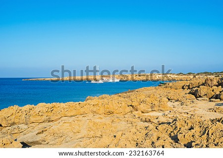 The yachts in the small harbor on Cape Greco, surrounded by yellow rocks and blue sea, Cyprus. - stock photo