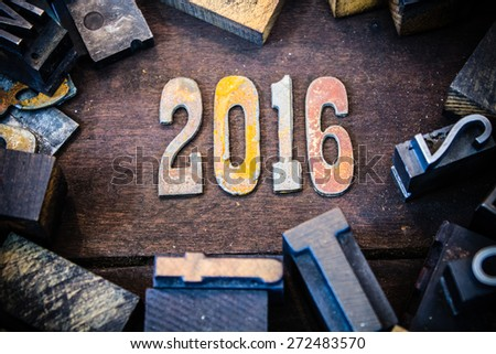 The year 2016 written in rusted metal letters surrounded by vintage wooden and metal letterpress type. - stock photo