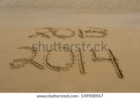 The years 2013 and 2014 are carved in the sand with the year 2013 being washed away by waves in this conceptual New Years photo