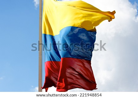 The yellow, blue and red of the Colombian flag billowing in the wind towards the camera. - stock photo