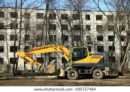 The yellow excavator against empty building - stock photo