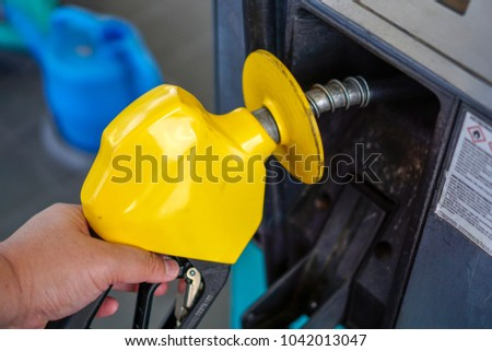 The yellow petrol pump handle at a petrol station. Filling fuel in a car