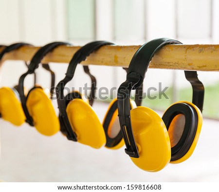 The yellow protective earmuffs for shooting . - stock photo