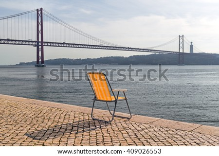 The Yellow Striped Chair Standing In Front Of The 25 De Abril Bridge, That  Connects