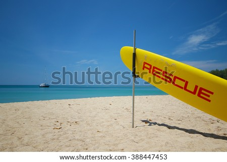 The yellow surf rescue board ready on the beach for accident prevention and water rescue on Nai Harn beach in Phuket thailand