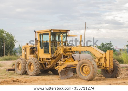 The yellow tractor parking on the ground - stock photo
