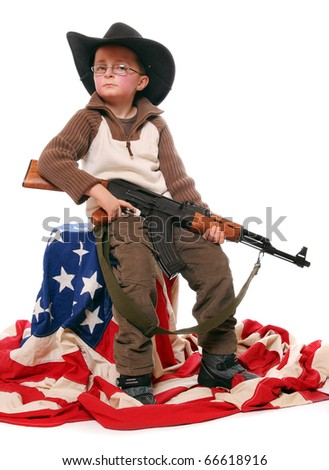The young  american patriot with assault rifle and cowboy hat sitting on a american flag.