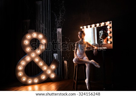 The young and beautiful ballerina is posing in the studio - stock photo