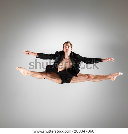 The young attractive modern ballet dancer in black jacket  jumping over gray background - stock photo
