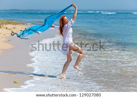The young attractive woman jumping with a blue scarf in hands