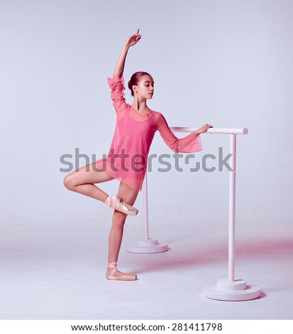 The young ballerina stretching on the bar on gray background - stock photo
