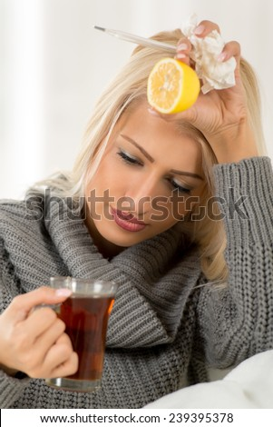 The young beautiful blonde girl with disappointment looking in a cup of tea she is holding. On the other hand, on which she leaned her head, holding a lemon, a thermometer and a crumpled handkerchief. - stock photo